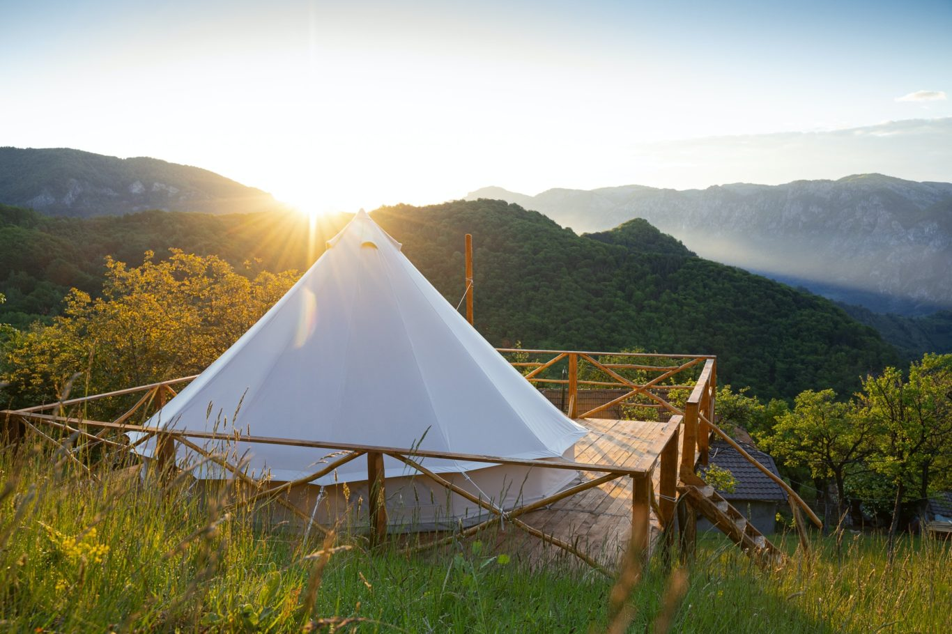 glamping tent in the morning sunlight with mountain range panorama